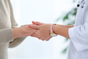 Doctor holding elderly patient hands on blurred background, closeup