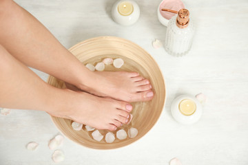 Woman soaking her feet in bowl with water and rose petals on floor, top view. Spa treatment