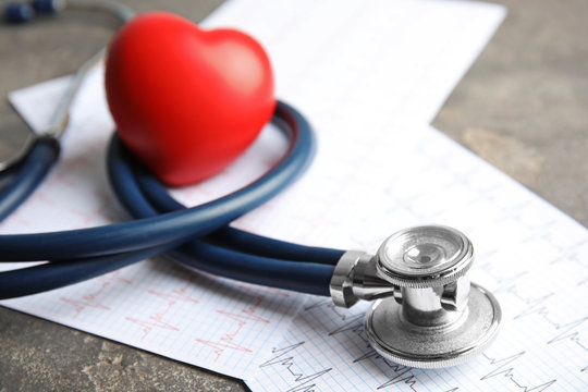 Stethoscope, red heart and cardiogram on gray table. Cardiology concept