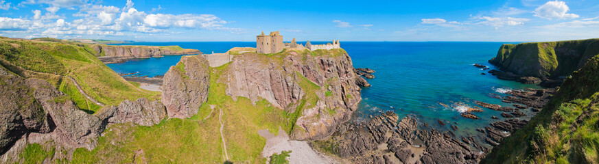 Panorama of a cliff with ancient castle in a bay with blue sky and white clouds in Dunnottar Castle, near Stonehaven, Aberdeenshire Wall mural