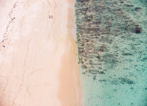 Vertical view of Pandawa Beach , Bali where 2 beachgoers are strolling next to each other with a calm beach