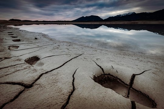Cracked, dry shore with footprints and water surface and Allgau Alps in the background, Forggensee, Fussen, Ostallgau, Bavaria, Germany, Europe
