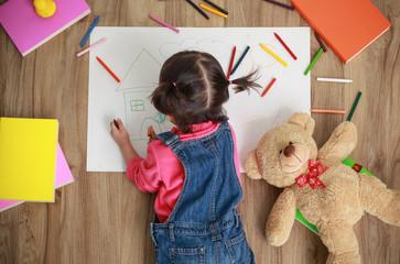 Little Asian girl drawing in paper on floor indoors, top view of child on floor