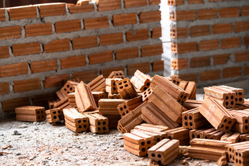 Stack of Brick preparing for mansonry over the photo blurred of Bricks wall background,