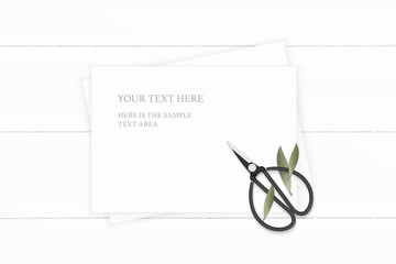 Flat lay top view elegant white composition paper nature leaf and vintage metal scissors on wooden background