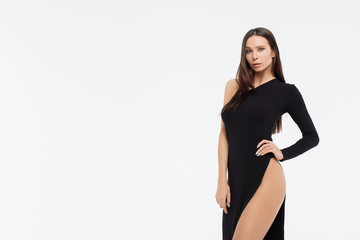 Woman with dreadlocks in elegant dress standing on light gray background
