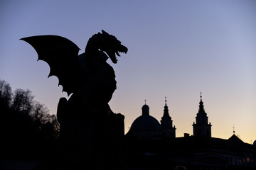 The fire Dragon symbol of the city of Ljubljana, seen on city bridge.  Night silhouette against purple sky, with skyline