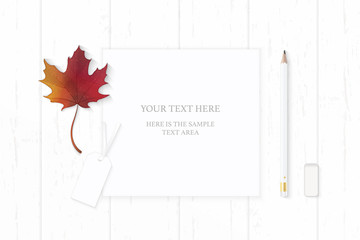 Flat lay top view elegant white composition paper pencil eraser autumn maple leaf and cardboard tag on wooden background