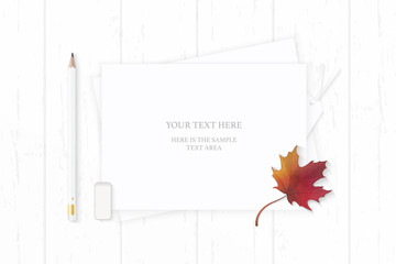 Flat lay top view elegant white composition pencil eraser tag and autumn maple leaf on wooden background