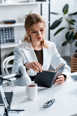 concentrated businesswoman in formal wear sitting at desk and reading notebook at workplace