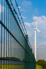 renewable energy concept: photovoltaic panels and wind turbines behind a fence against dramatic sky