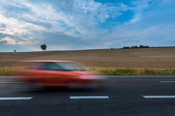 Cars driving on newly paved and marked road with corn fields in the background