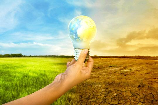 Human hands holding earth inside the light bulb