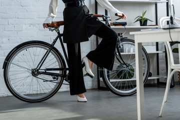 partial view of woman in black formal wear with bicycle