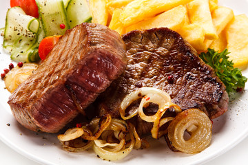 Grilled beefsteak with french fries and vegetable salad on white background