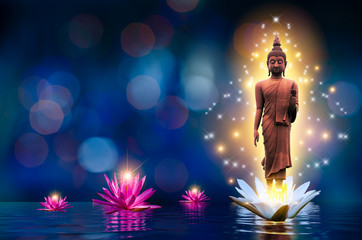 The Buddha statue stands on a white and pink lotus in the water. Bokeh blue background.