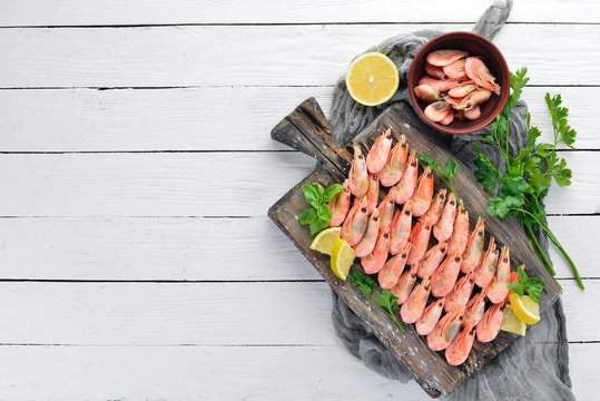 Shrimp on a wooden board. Seafood. On the old background. Top view. Free copy space.