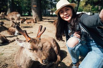 woman taking selfie with sleeping deer