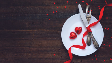 Valentine's Day Festive table setting, flat lay with two red heart shape chocolate candies on white plate, fork, knife and red ribbons on wooden table. Valentine Day, love, dating concept, copy space