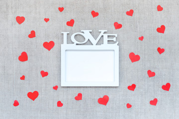 Valentines Day mockup with white frame with word LOVE and many red hearts on linen fabric background.  Valentine Day, love, romance, dating concept, copy space