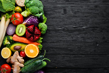 Fresh vegetables and fruits. Organic food on a black wooden background. Top view. Free copy space.