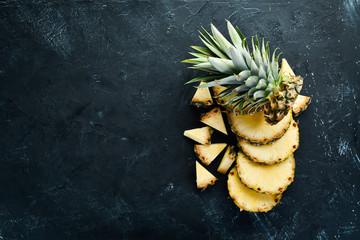 Sliced pineapple on a black background. Tropical Fruits. Top view. Free copy space. Wall mural