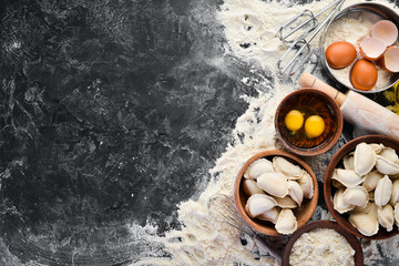 Dumplings with potatoes. Vareniki Homemade. Flour, eggs, dough on a black background. Top view. Free copy space.