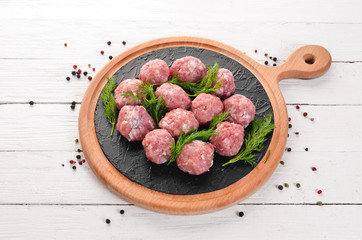 Raw meat balls. On a white wooden background. Top view. Free copy space.