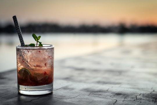 strawberry caipirinha mixed cocktail drink in outdoor bar at sunset