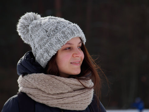 Happy young woman  in winter hat and scarf in the winter park in sunny day