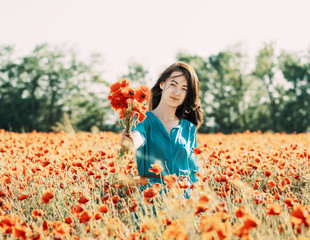 Smiling woman with bouquet of poppies.