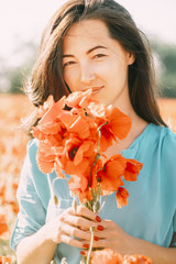 Outdoor portrait of beautiful woman with poppies.