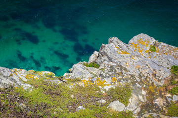 Rocky coast and emerald ocean water top view