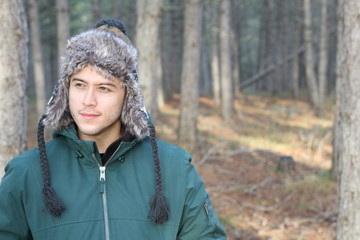 Ethnic man with winter hat in the forest