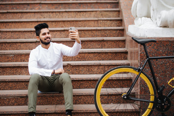 Excited young asian man sitting on stairs with bicycle, make video call or translation in blog with mobile phone