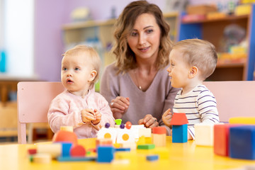 Children with teacher playing educational toys, stacking and arranging colorful pieces. Learning through experience concept, gross and fine motor skills.