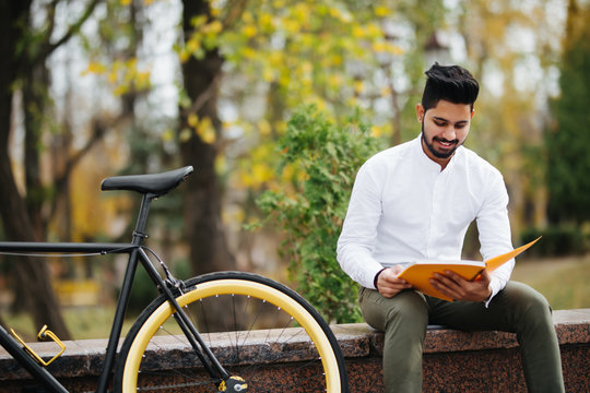Young indian man reading a book while taking a break on the city street