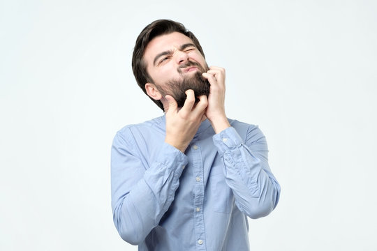 Young spanish man with black beard scratching his face