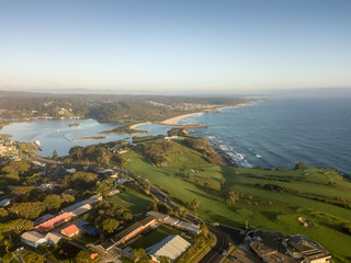 An aerial shot of the town, golf course, river mouth and coast of south coast town of Narooma, New South Wales, Australia