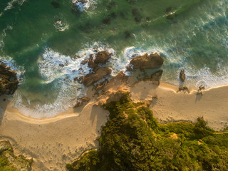 An aerial shot of the shoreline of a beach in Narooma on the South Coast of NSW, Australia