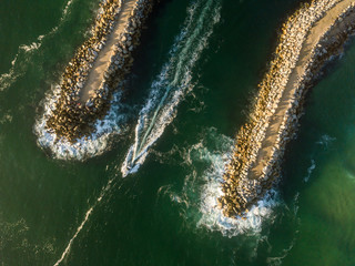 An aerial shot of a boat travelling between two break walls  at sunrise