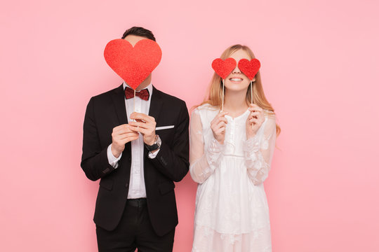 Loving couple in love, man and woman with red hearts on their eyes, over pink background. Lovers day concept