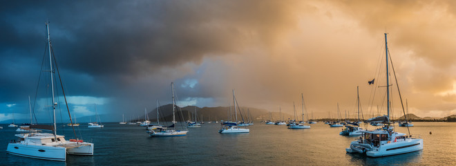 Anchored sailing boats and catamarans on calm sea with tropical storm on background