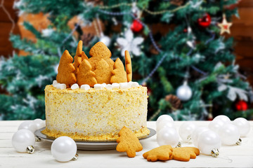 Homemade honey cake decorated with white cream, cookies and marshmallow on white wooden table against blurred background