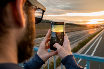 Guy taking a photo with his mobile phone at sunset. Photo style social networks