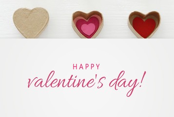 Valentine's day concept. hearts as paper gift boxes over wooden white background.