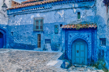 Deurstickers In the Medina of Chefchaouen, all the houses are painted blue, like the one we see in this image. An old house but beautifully decorated. Morocco.