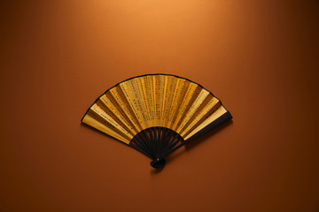 top view of decorative black and golden fan with hieroglyphs on brown background, chinese new year concept