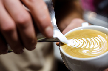 Closeup of making beautiful latte art with milk in an espresso cup