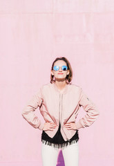 Portrait of young woman wearing sunglasses posing in front of pink wall